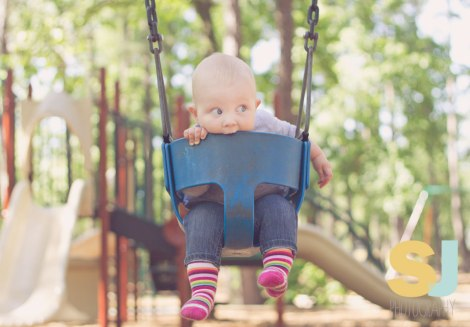 a baby at the park in a swing
